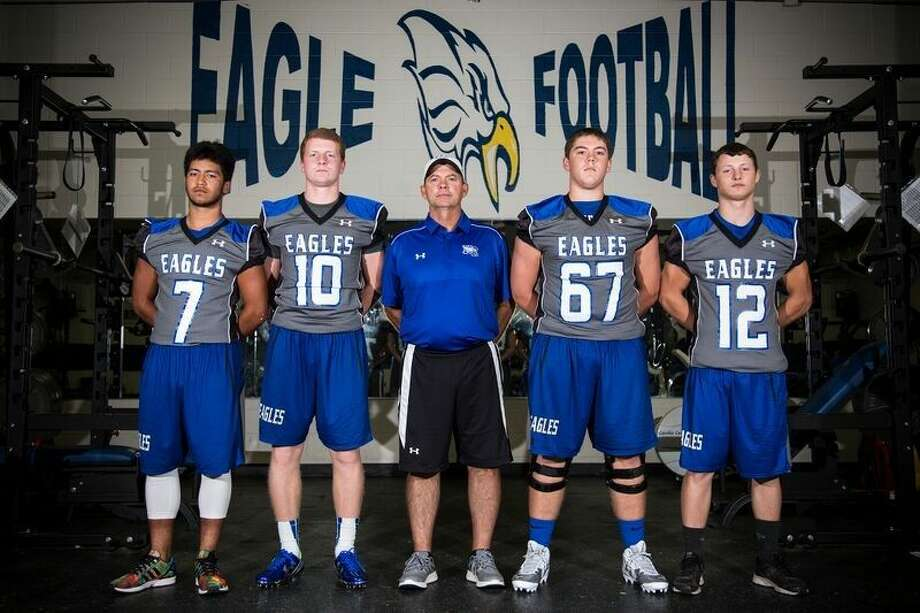 Eagles free safety Anthony Ponce (7), quarterback Timmy Ware (10), head coach Brady Pennington, offensive lineman Jacob Carroll (67) and cornerback Kyle Lolley (12) pose for a portrait Aug. 13, 2015, at New Caney High School.