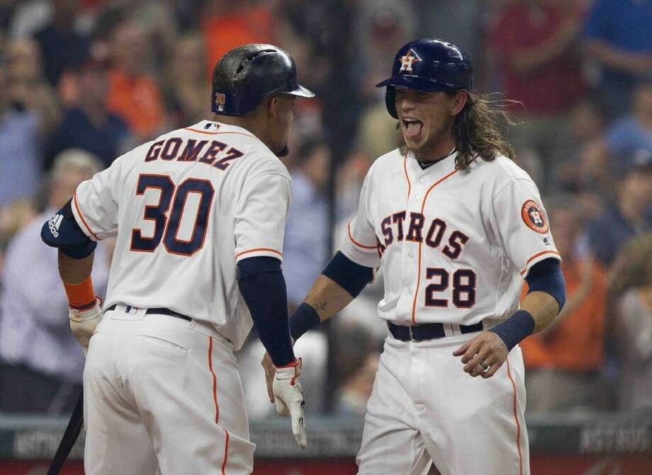 Houston's Colby Rasmus celebrates with Carlos Gomez after Rasmus' two-run home run during the first inning of an MLB baseball game at Minute Maid Park Monday.