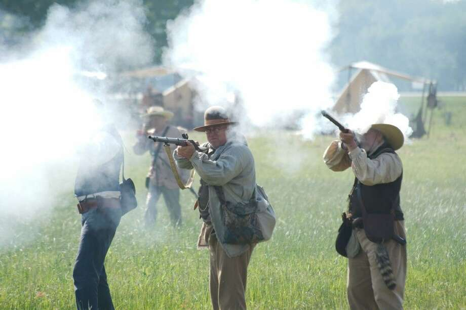 History enthusiasts wear replica clothing and fire historically accurate muskets used by Sam Houston's Texas volunteer army in the Battle of San Jacinto during a reenactment of the battle Saturday, April 23.
