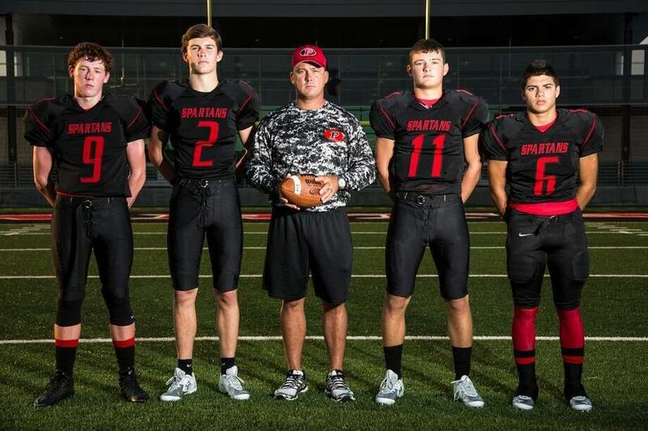 Spartans defensive back Tyler Crochet (9), wide receiver Shane Carney (2), head coach Reno Moore, quarterback Jake Hall (11) and wide receiver Tyler Baker (6) pose for a portrait Aug. 13, 2015, at Texan Drive Stadium in New Caney.