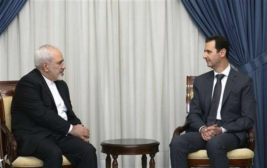 Iranian Foreign Minister Mohammad Javad Zarif, left, who negotiated his country's nuclear deal with world powers, discussed ways of ending Syria's civil war with President Bashar Assad in Damascus on Wednesday as attacks surged around the Syrian capital, killing tens of people and wounding dozens. Photo: Uncredited