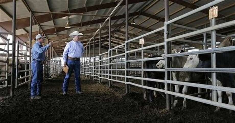 Hutchison, right, makes a visit to the Giddings Livestock Commission, June 22, in Giddings. Photo: Eric Gay