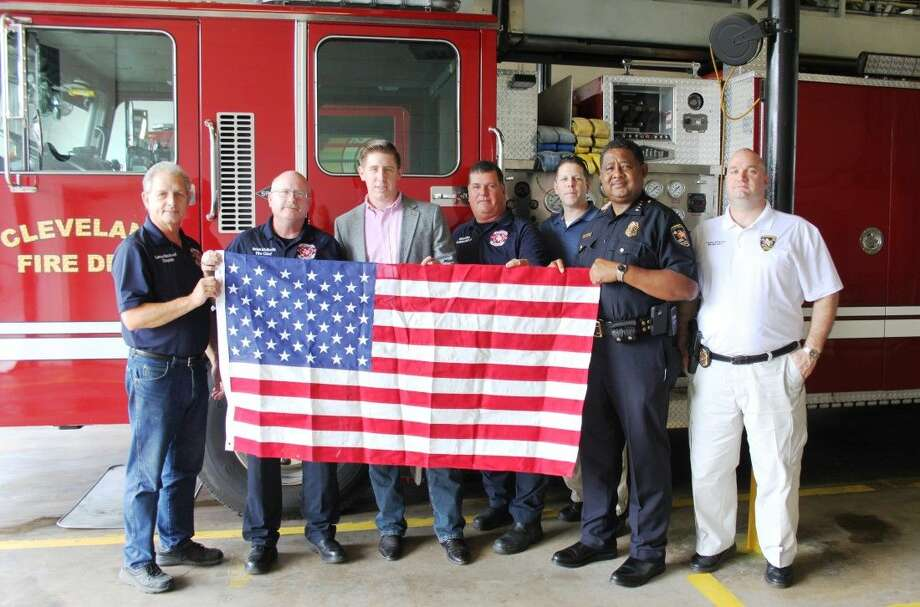 Staff photo by Vanesa BrashierDavid Covey (third from left) with U.S. Congressman Steve Stockman's Office made a special delivery of an American flag to Cleveland Fire Department on Sept. 11, 2014. The flag is one of many that flew over the U.S. Capitol building in Washington, D.C., for the 13th anniversary of the 9/11 terror attacks. Early Thursday morning, Covey hopped a flight to the Houston area and drove to Cleveland to hand-deliver the flag to Cleveland Fire Department. Pictured accepting the flag is Cleveland Fire Chief Brian McNevin (second from left). Also pictured are Chaplain Lance Blackwell and Clifford Wise representing the fire department and Cleveland Police Chief Darrel Broussard, Capt. Scott Felts and Det. Investigator John Shaver. Photo: VANESA BRASHIER