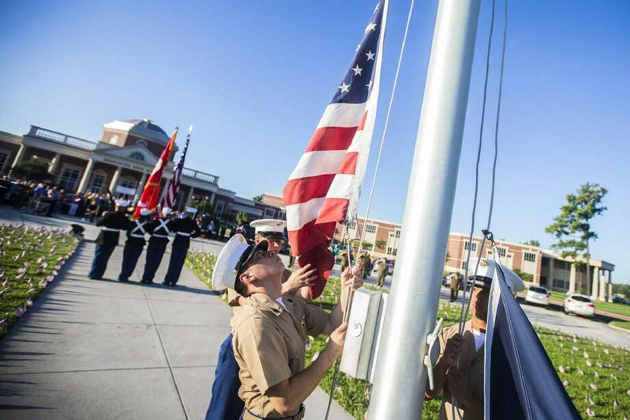 Staff photo by Andrew BuckleyMembers of the Marine Corps JROTC raise the American and Texas flags during a 9/11 remembrance ceremony Sept. 11, 2014, at Atascocita High School. Photo: ANDREW BUCKLEY