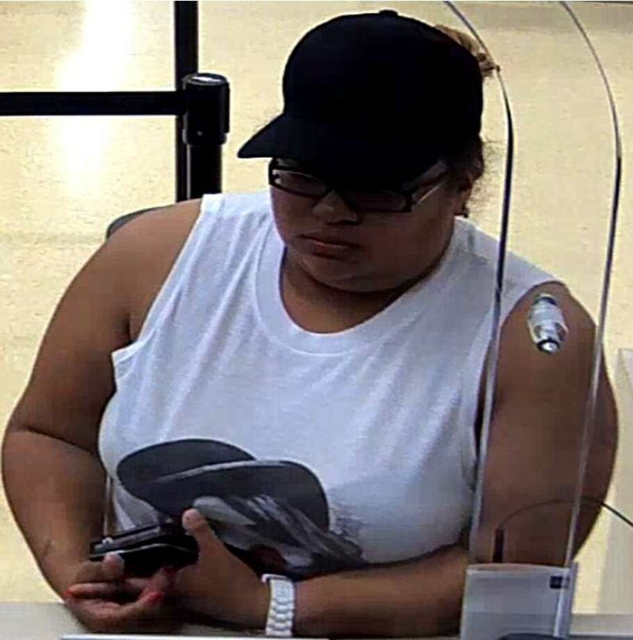 SubmittedOne of the two suspect wanted in an 8,000 check forgery case, described as a Hispanic female in her late 20s or early 30s, wearing a white, sleeveless t-shirt, a black baseball cap and black-framed glasses. Photo: Submitted