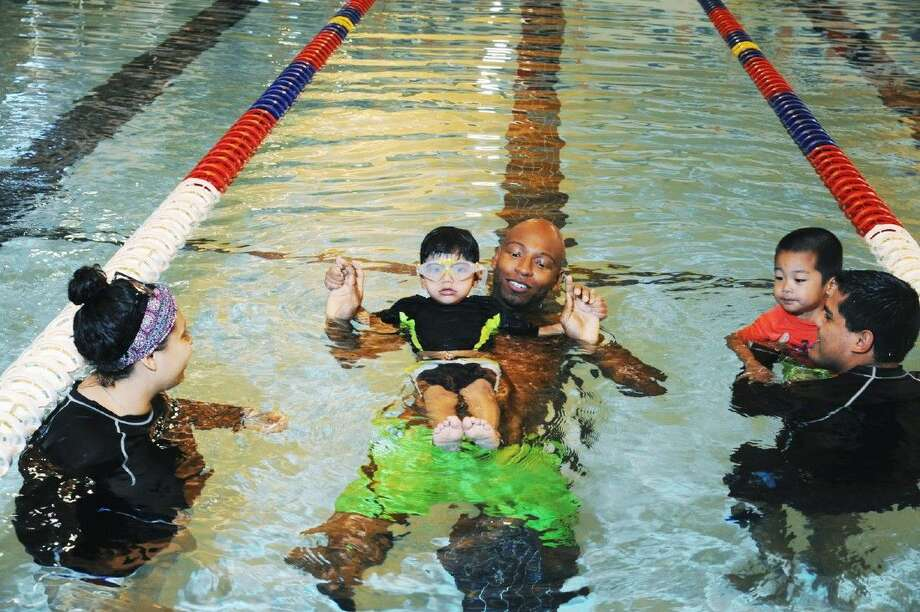 Olympic swimmer Cullen Jones teaches a child floating techniques at the Tompkins High School pool in Katy on Friday, April 22. Photo: Tony Gaines