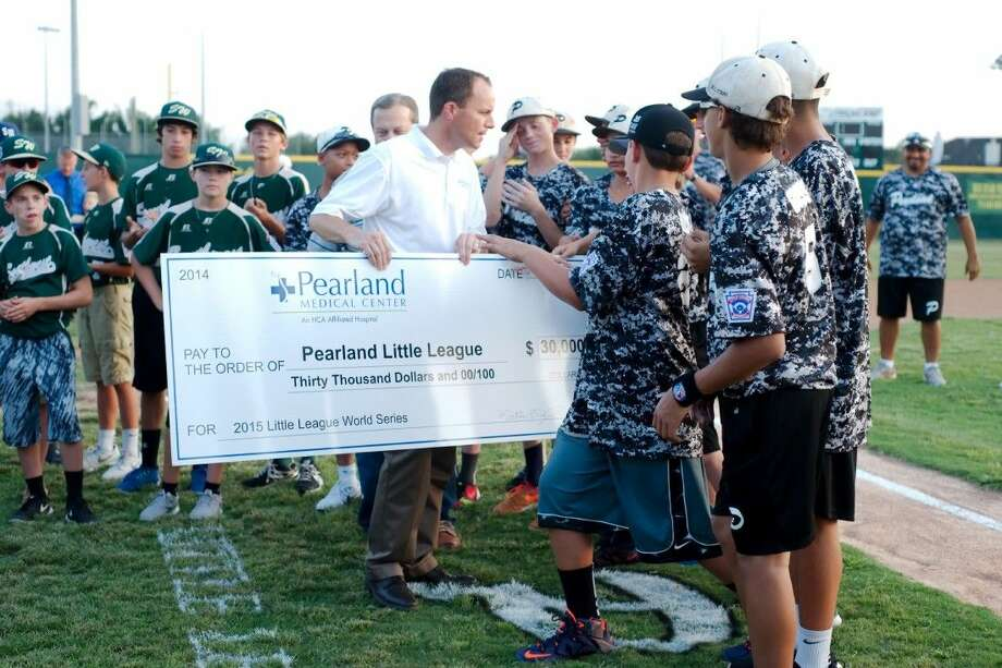 Pearland West Little League players admire a $30,000 check provided by Pearland Medical Center CEO Matt Dixon during a fundraising event to send the team to the Little League World Series.