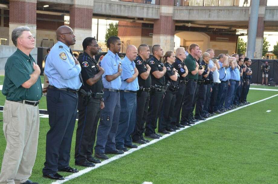 Submitted PhotoLocal first responders participate in the playing of the national anthem prior to the Cypress Falls vs. Langham Creek football game on Thursday at the Berry Center, which marked the 13th anniversary of the September 11 attacks. Photo: Submitted Photo