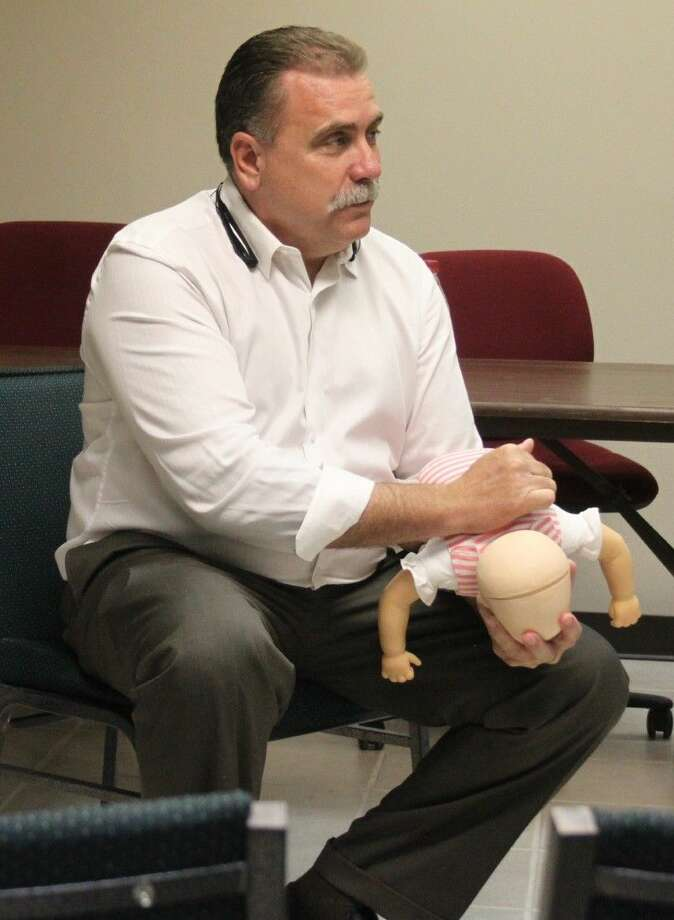 Rick Smith uses a baby mannequin to properly demonstrate hitting in between its shoulders in the event of choking. Photo: Jacob McAdams