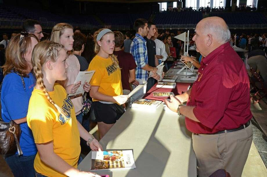 Submitted PhotoBoard of Trustees member Bob Covey represents his alma mater, Texas State University, as he greets CFISD students during the 2013 College Night. Photo: Submitted Photo