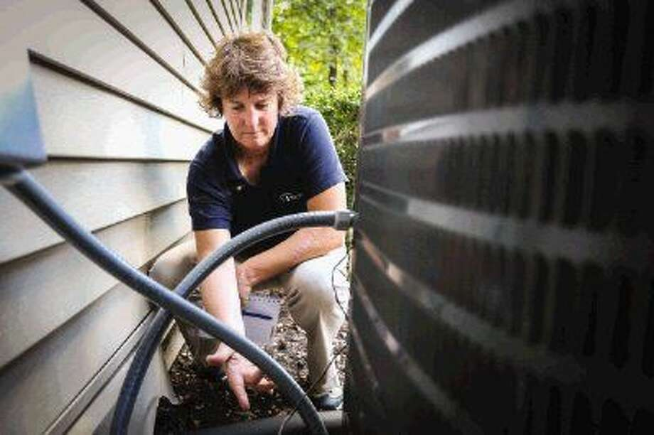 Photo by Michael Minasi Sybil Bradley, a certified home inspector through Pillar To Post Home Inspectors, demonstrates some of the items she would look for while inspecting an air conditioning unit at her home in Conroe. Photo: Michael Minasi