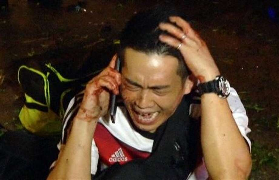 A man talks into a mobile phone after a large explosion rocked a central Bangkok intersection on Monday during the evening rush hour, killing a number of people and injuring others. Photo: Uncredited