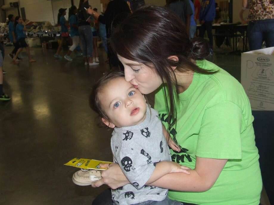 Celeste Garza, a storm victim, kisses her son while waiting for assistance at the Klein ISD Multipurpose center on Friday, April 22.