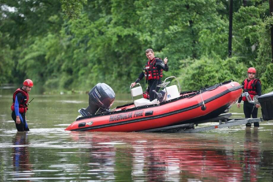 Magnolia firefighters search for stranded residents on Monday, April 18, in Pinehurst on Vallie Street.