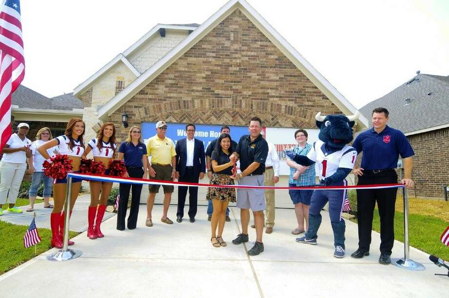Kevin and Carolina Bone cut the ribbon to there new home surrounded by the representatives of the Houston Texans and Operation Finally Home, Pulte Homes and FMC Technologies. Photo: Tony Gaines