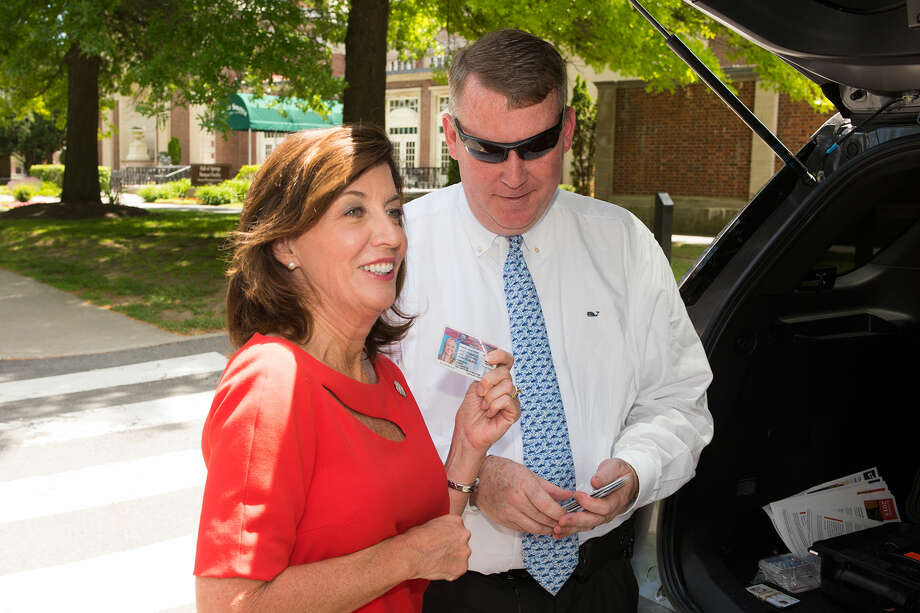 Lt. Gov. Kathy Hochul looks at confiscated fake IDs with a Department of Motor Vehicles investigator after she announced a statewide underage drinking sweep of summer concerts June 15, 2016 at the Saratoga Performing Arts Center. (New York State DMV)