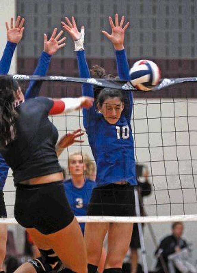 Friendswood's McKenna Fridye causes the the Winston Churchill San Antonio player to spike the ball in the net during play at the Adidas Invitational. Photo: Kar B Hlava