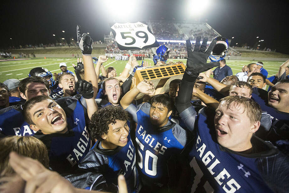 The Eagles celebrate with their trophy after New Caney's 58-33 victory over Porter in the Battle Line on 59 rivalry game Sept. 12, 2014, at Texan Drive Stadium in Porter. Photo: Andrew Buckley