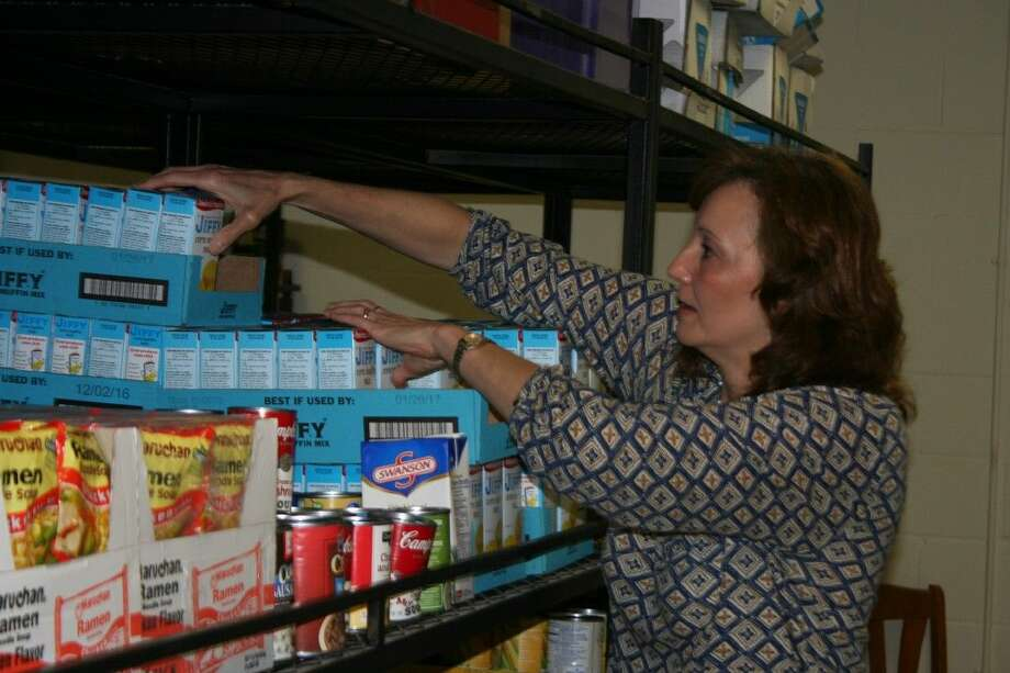 Volunteer Charlie Easter works to organize a few of the shelves at the Huffman Food Pantry.