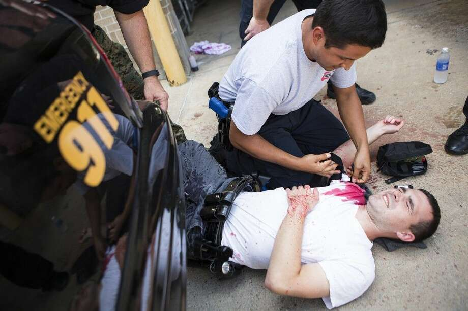 Thomas Meek, bottom, is treated for a gunshot wound by Marvin Rivera during a training session for potential SWAT members Aug. 18, 2015, at the Humble Police Department. Photo: ANDREW BUCKLEY