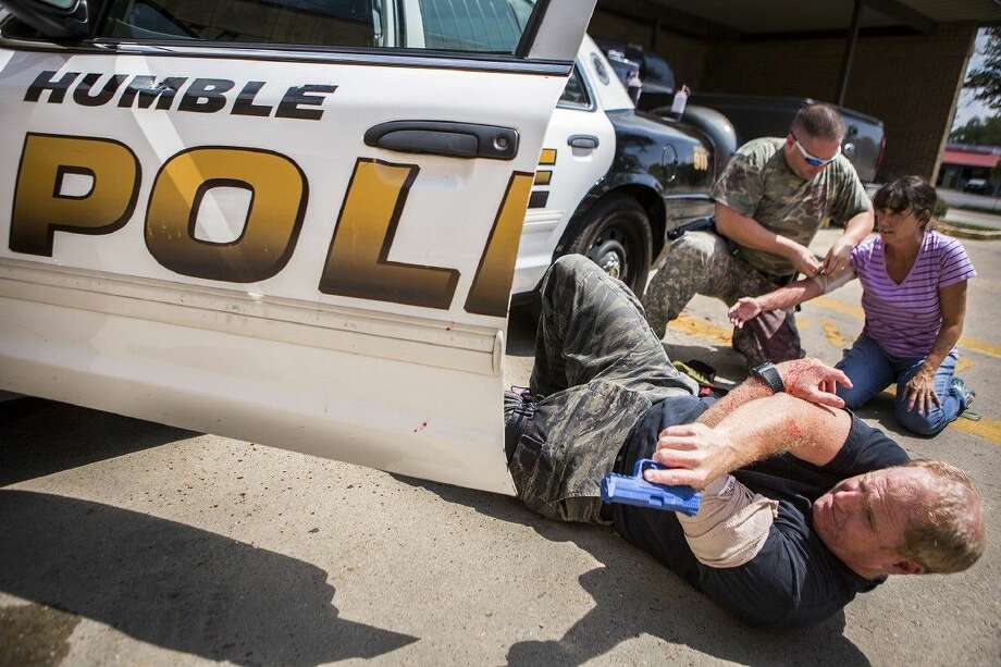 A wounded Jim Hammock, bottom, covers Kent Guidry as he treats Kathy McLaughlin, a victim of a domestic violence attack, during a training session for potential SWAT members Aug. 18, 2015, at the Humble Police Department. Photo: ANDREW BUCKLEY