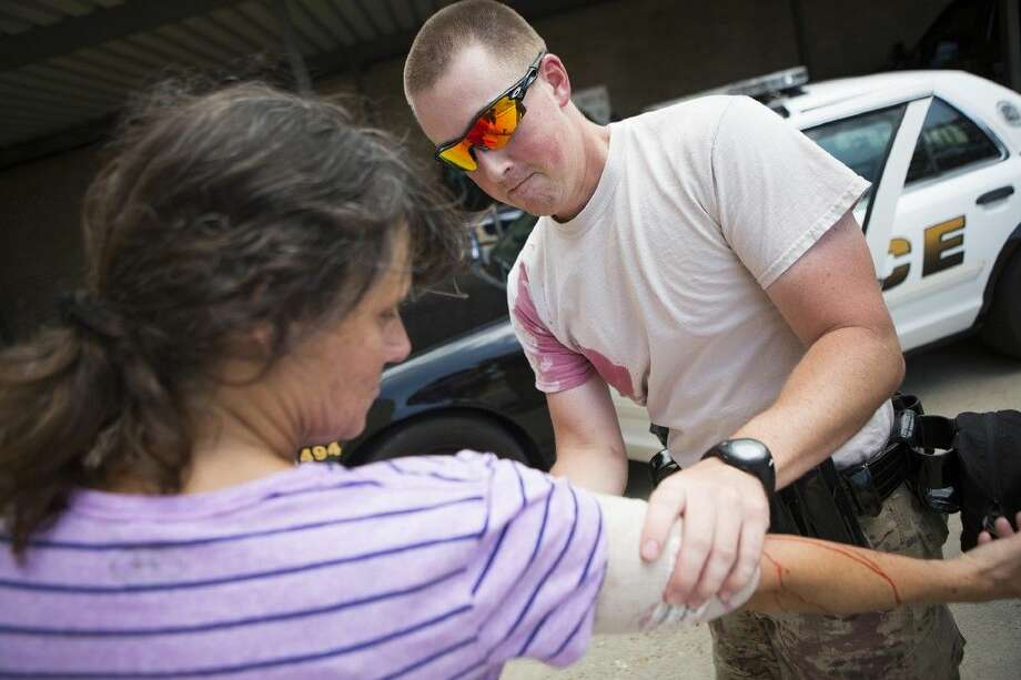 Cody Deal bandages the arm of Kathy McLaughlin, a victim of a domestic violence attack, during a training session for potential SWAT members Aug. 18, 2015, at the Humble Police Department. Photo: ANDREW BUCKLEY