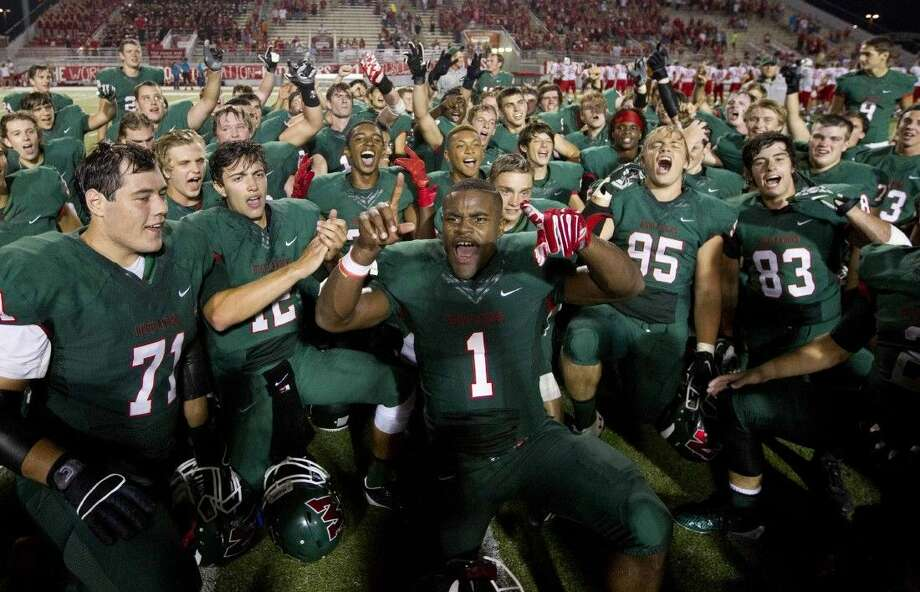 Staff photo by Jason FochtmanPatrick Carr (1) and The Woodlands celebrate after the Highlanders defeated Katy 24-7 to break the Tigers' 50-game regular-season winning streak during a high school football game at Woodforest Bank Stadium Friday. To view or purchase this photo and others like it, visit HCNpics.com.