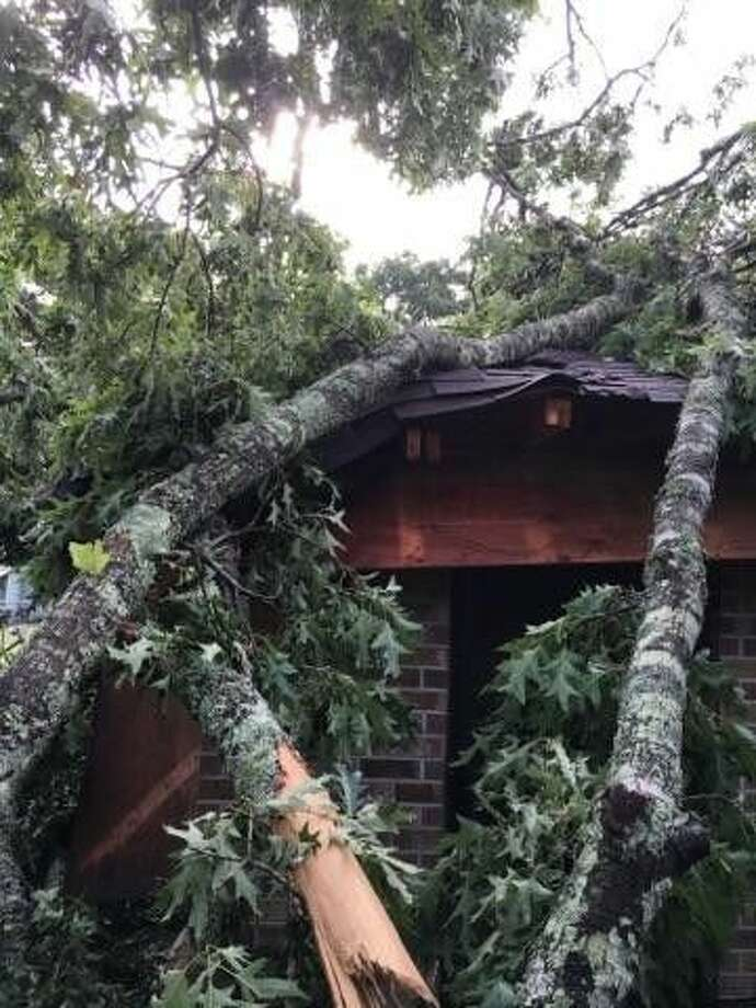 A neighbor's massive oak tree tore through a section of the Tarkington home of Richard and Devida Jarvis around 5 a.m. Tuesday, April 27. Photo: Submitted