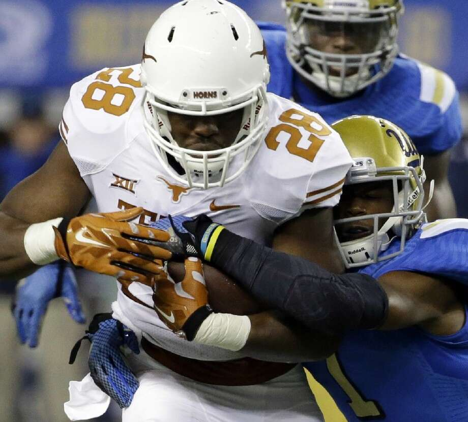 AP photoTexas running back Malcolm Brown (28) is tackled by UCLA defensive back Ishmael Adams. UCLA won 20-17. Photo: Tony Gutierrez