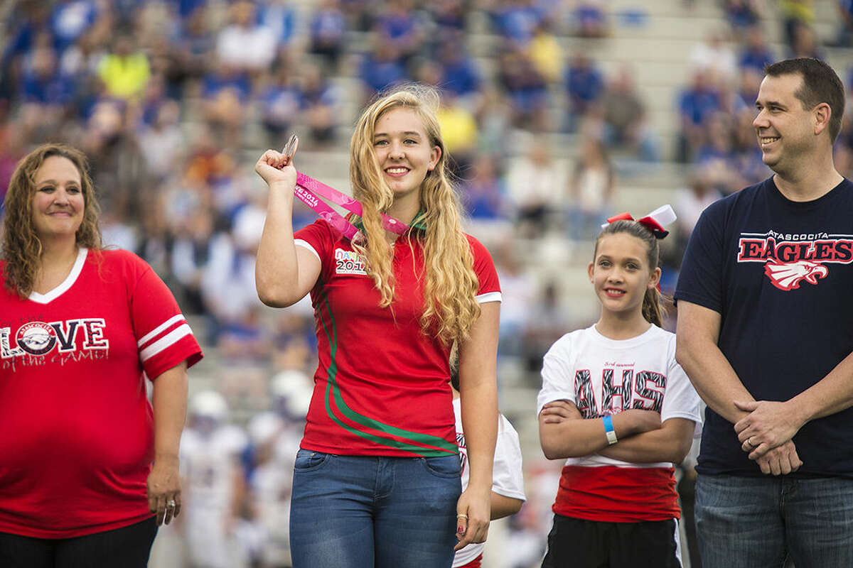 Kelsey Brann shows off her bronze medal from the 2014 Youth Olympics as she is honored during Atascocita's 14-10 victory over Klein on Sept. 13, 2014, at Turner Stadium in Humble.