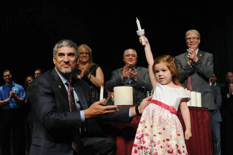 """Brylie Hinkelman holds up a candle during a special """"candle of new beginning"""" ceremony along with Dr. Todd Stephens on Monday, August 17 2015."""