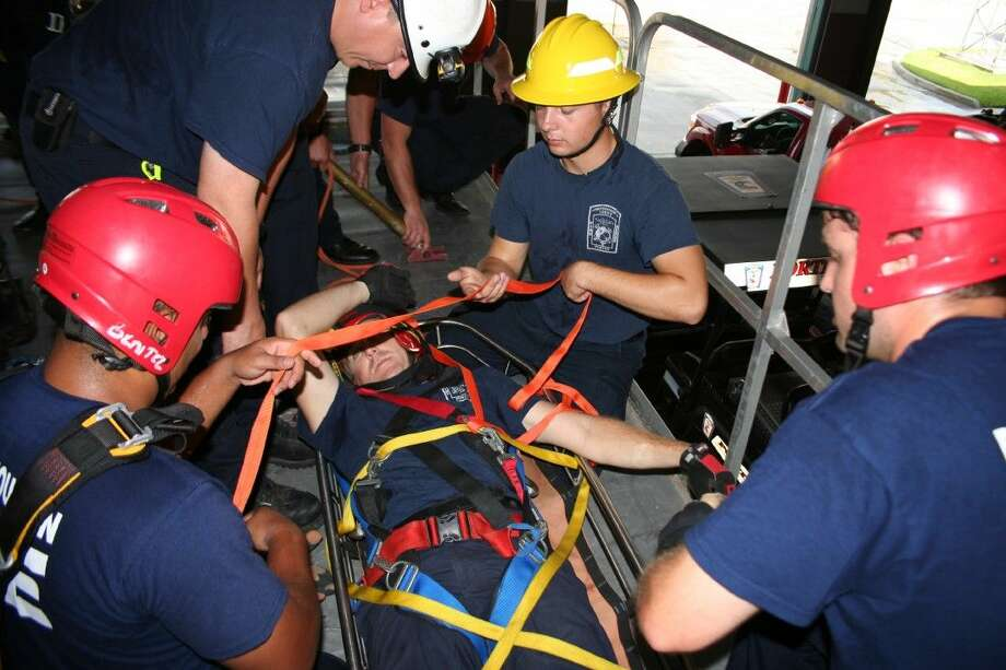 """Porter, South Montgomery and Port of Houston Fire Departments' firefighters work to secure an """"injured"""" person during the Confined Space Rescue training Aug. 19, 2015."""