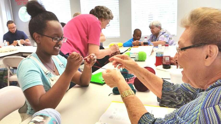 """Pictured is """"Happy Hands"""" member Deborah Cloessner with one of the fast learning crochet kids. Photo: Submitted"""