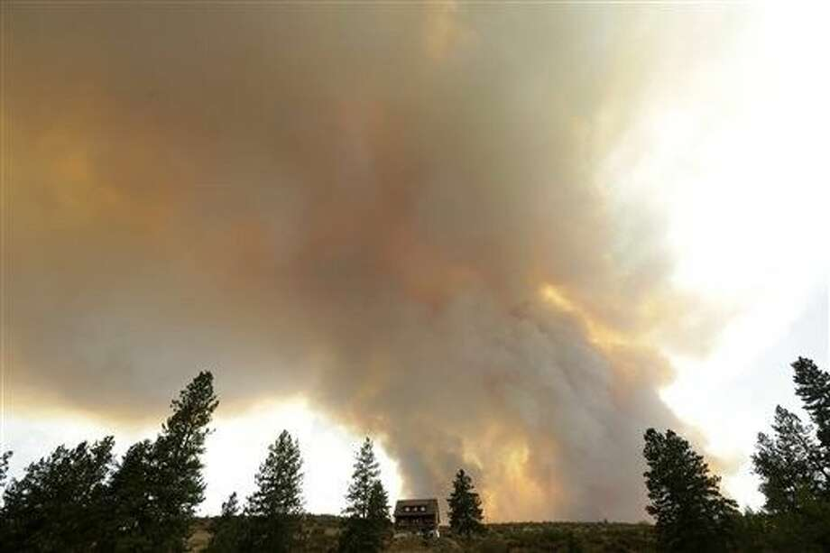 Smoke from an approaching wildfire looms over a home near Twisp, Wash., Wednesday Authorities on Wednesday afternoon urged people in the north-central Washington town to evacuate because of a fast-moving wildfire. Photo: Ted S. Warren