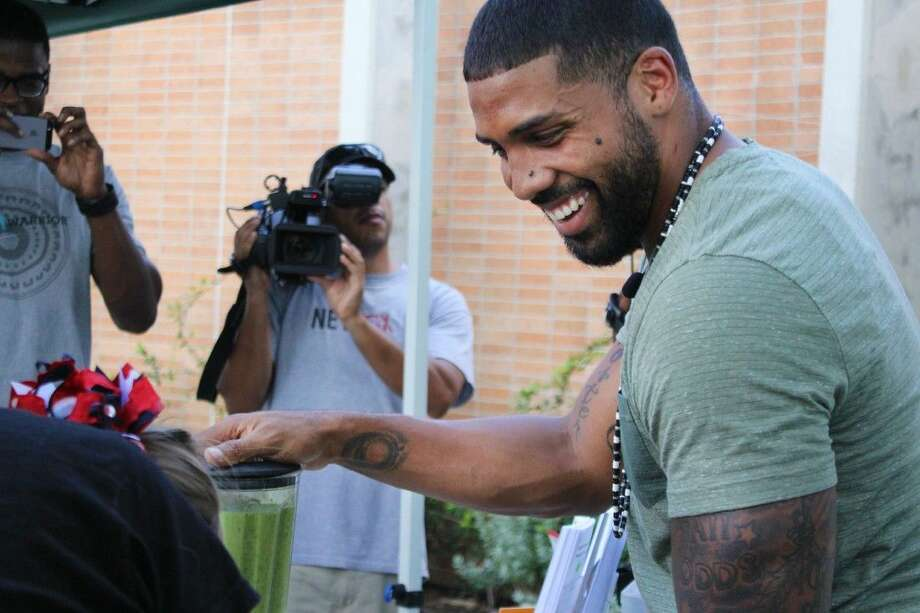 Staff photo by Minza KhanArian Foster engages with a young fan during his smoothie demo on the Whole Foods patio.