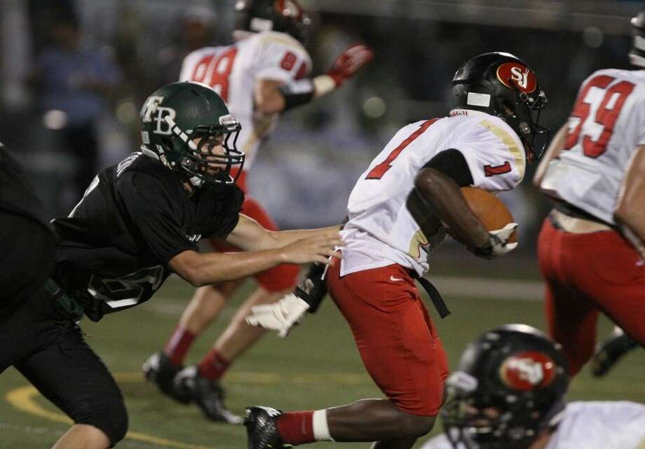 St. John XXIII's Ja'antre Minix runs against Fort Bend Christian Academy's Bobby De St. Remey during a 2014 non-district game in Sugar Land. Photo: HCN File Photo