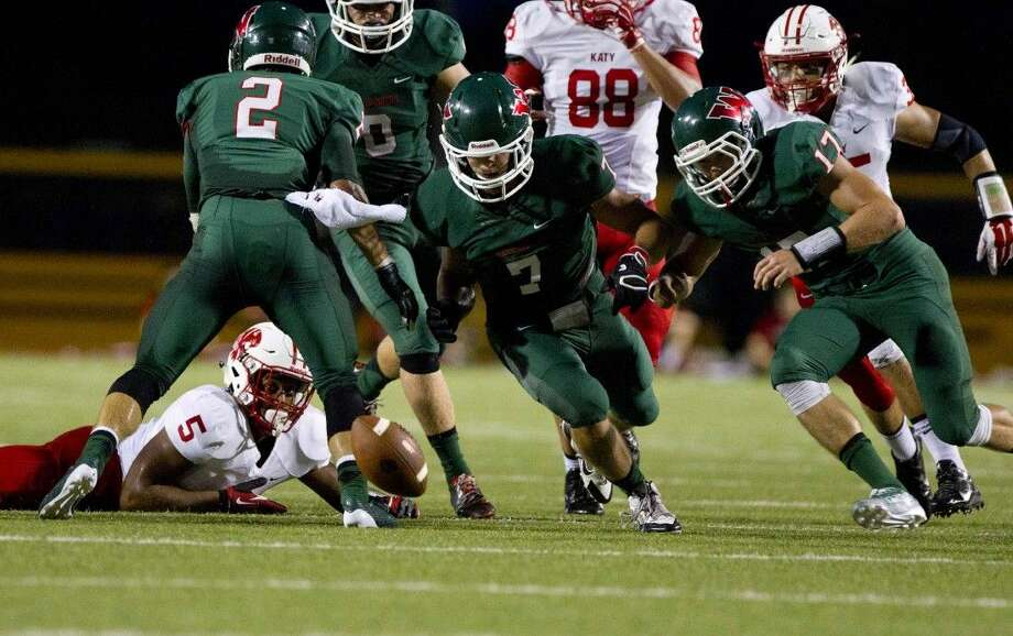 The Woodlands linebacker Tristan Horton (7) recovers a fumble by Katy running back Kyle Porter in last year's game at Woodforest Bank Stadium. The Highlanders won that game 24-7. The Woodlands travels to play Katy on Friday night at Rhodes Stadium in Katy.