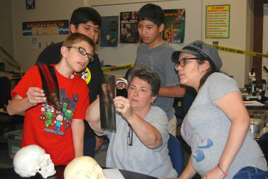 Lee College biology instructor Margene Lenamon (center) helps Kids at College participants analyze an x-ray of a human bone during the Forensic Science summer camp held in 2015. Registration is now open for the 2016 Kids at College program, which will include camps and courses at the main campus in Baytown and the Lee College Education Center - South Liberty County.