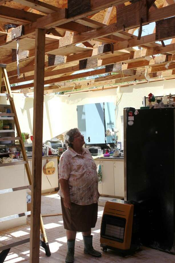 Anna Benoit peers up through the open roof of her family's gathering room. The small wood-framed structure was built solely for the purpose of hosting Benoit family gatherings near the family members' homes in Rayburn, but Anna also uses it for quilting. The roof of the structure was ripped off by the storm system that passed through Liberty County on April 27. Photo: Vanesa Brashier