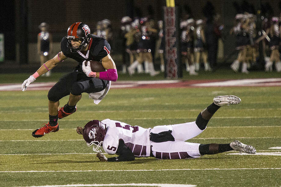 Falcons wide receiver Chase Harrell jumps over a defender during Huffman's victory over Silsbee on Oct. 3, 2014, at Hargrave High School.