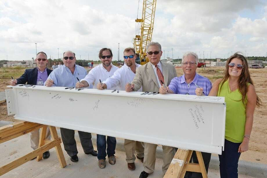 Representatives from CFISD and Satterfield & Pontikes Construction, Inc., put their mark on the final beam for Cypress Park High School on Aug. 19. Pictured (L-R) are Dan Grosz, CFISD director of design and facilities planning; Charlie Fote, Satterfield & Pontikes executive vice president; Eric Hogan, Satterfield & Pontikes project manager; Eric Blankenship, Satterfield & Pontikes project executive; George A. Pontikes, Jr., Satterfield & Pontikes president; Roy Sprague, CFISD associate superintendent of facilities and construction; and Sarah Stolting, PBK assistant project manager.