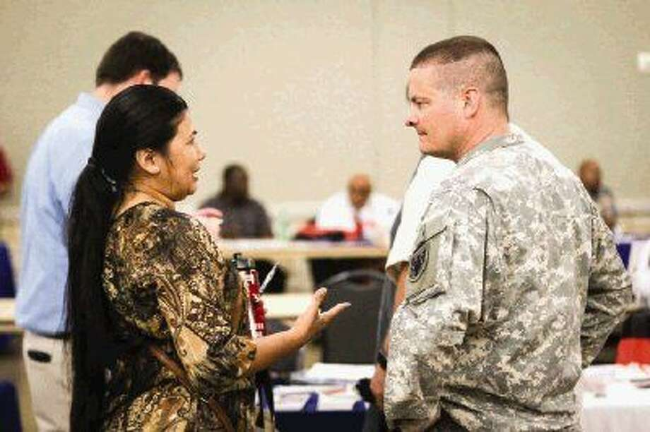 Sgt. Scott McGovern, of Lone Star Airport Aviation, left, and Trish Quintanilla, an Air Force veteran who works with Conroe Appliances, chat about ways to hire more veterans on Tuesday at the Lone Star Convention and Expo Center.
