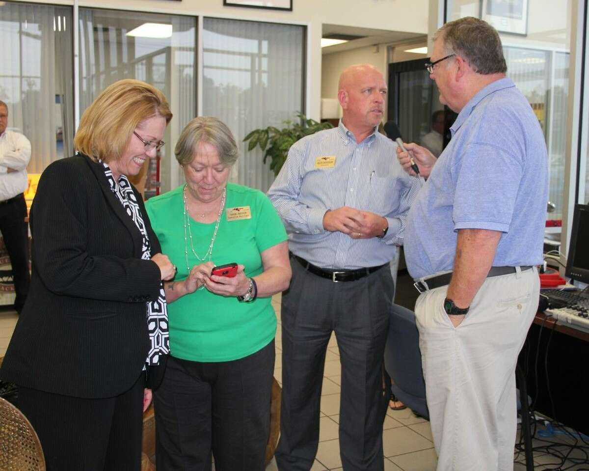 Jeff McClain, station manager of KORG-LP FM in Cleveland, interviews Buck Anderson of Anderson Ford Mercury regarding a drawing for a new Ford Fiesta held by Keep Cleveland Beautiful. Cleveland Lions Club had the winning ticket. Pictured at right are KCB President Frieda Joyce and Sharon Anderson as they contacted Lions Club members to notify them of the win.