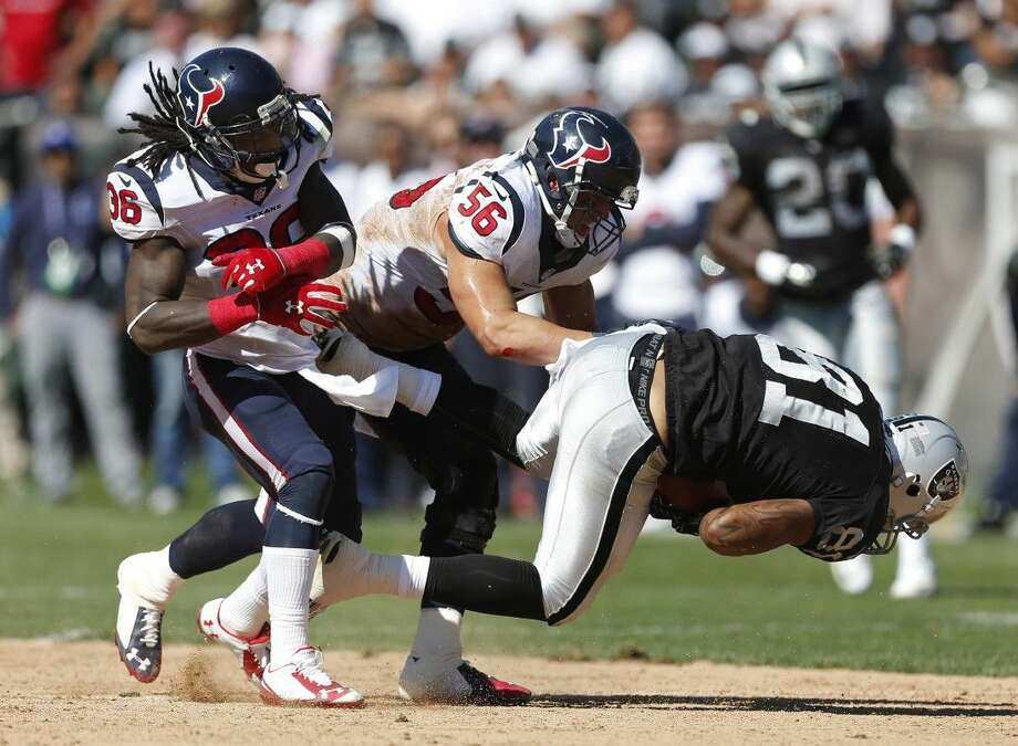 AP photoTexans defenders D.J. Swearinger, left, and Brian Cushing bring down Raiders tight end Mychal Rivera. The Texans forced four turnovers in Sunday's win over the Raiders. Photo: Beck Diefenbach