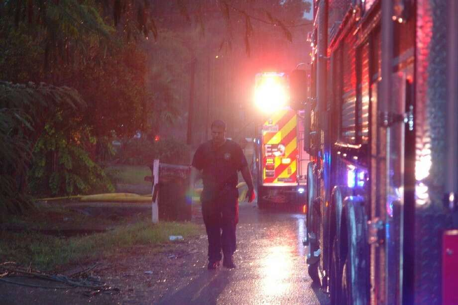 A Conroe firefighter walks back to a fire engine in the rain after assisting other firefighters in a house fire early Thursday. No one was inside the home at the time of the fire.