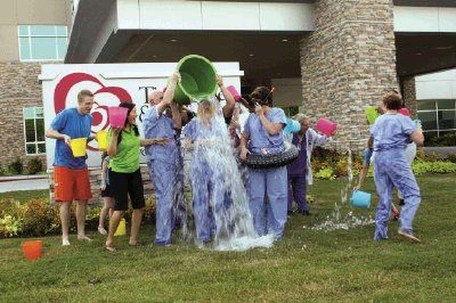 SubmittedMelinda Stephenson, CEO of Kingwood Medical Center, is doused with a large bucket of ice cold water after accepting the challenge to raise awareness for the ALS Association.