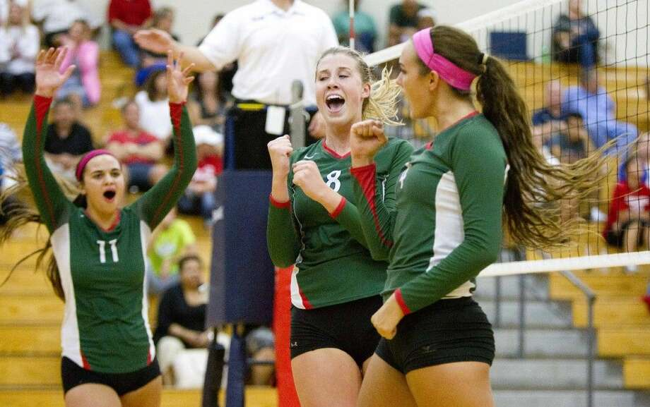 Staff photo by Jason FochtmanFrom left, The Woodlands' Courtney Quinn, Rachel Reed and Kendall Cook celebrate Cook's kill against Atascocita on Tuesday at The Woodlands High School. To view or purchase this photo and others like it, visit HCNpics.com.