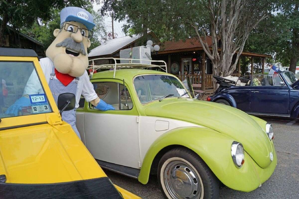 Tomball tourism mascot Rusty Rails loves on the classic VWs at Bugs, Brew & Barbecue.