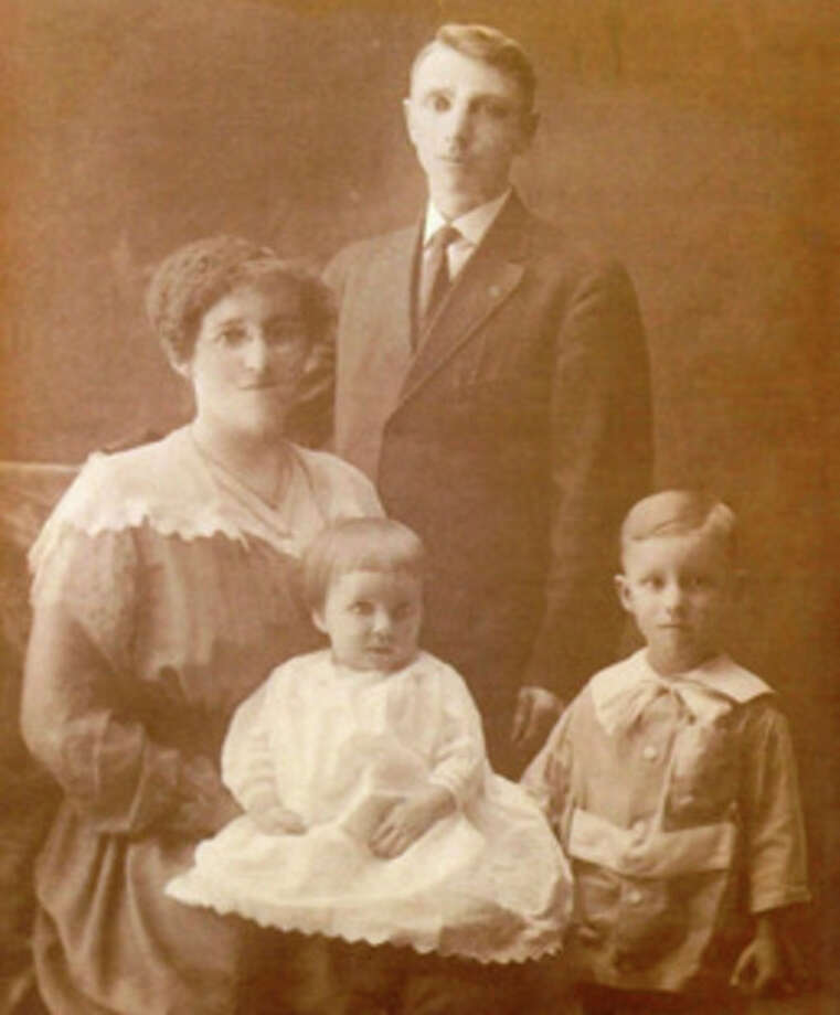 Proud parents Verna and William Wark pose with their two children.  Rhea is the baby on her mother's lap with big brother Purl standing beside her.  William Wark was a rural mail carrier in Peck.  Rhea was born July 29, 1916.