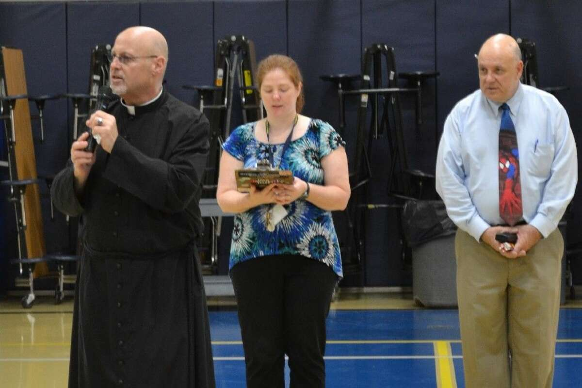 The Rev. Thomas Hopper - along with Tabitha Madrid, junior high religion teacher,and Principal Joseph Noonan - lead students in morning prayer during convocation at St. Anne's Catholic School.